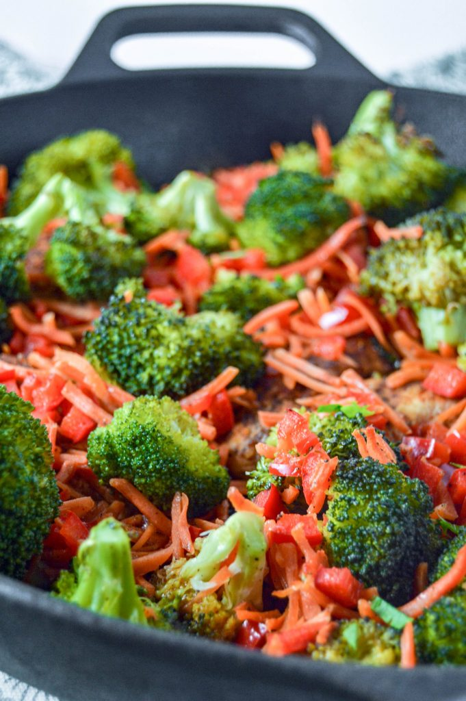 Angled, close up side view of a cast iron skillet with chicken, broccoli, carrots, and red peppers.  Cast iron is sitting on a teal and white towel. www.atwistedplate.com