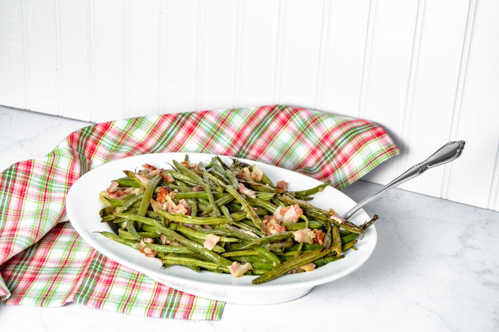 "Pinterest Image for Perfectly Roasted Potatoes. Top picture is Bacon Green Beans in a white oval bowl with a silver spoon sticking out on the right hand side. The background is white with a red/white and green plaid towel. Below in white letters with a green background it says ""Bacon Green Beans"". Below is a close up side view Bacon Green Beans in a white oval bowl with a silver spoon sticking out on the right hand side. The background is white with a red/white and green plaid towel. www.atwistedplate.comwww.atwistedplate.com/bacon-green-beans/"