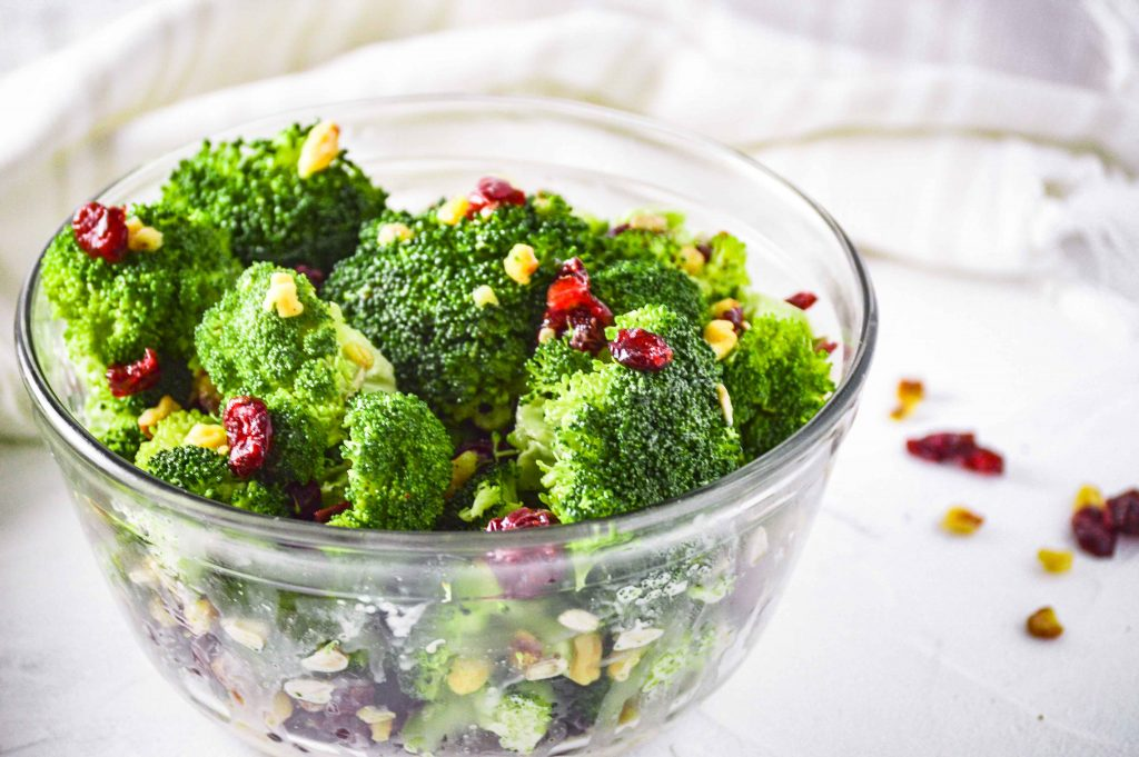 Close up side angled view of Broccoli salad in a clear bowl against a white background. there are walnuts and dried cranberries scattered around and a white towel behind the bowl of broccoli salad. https://www.atwistedplate.com/broccoli-salad/