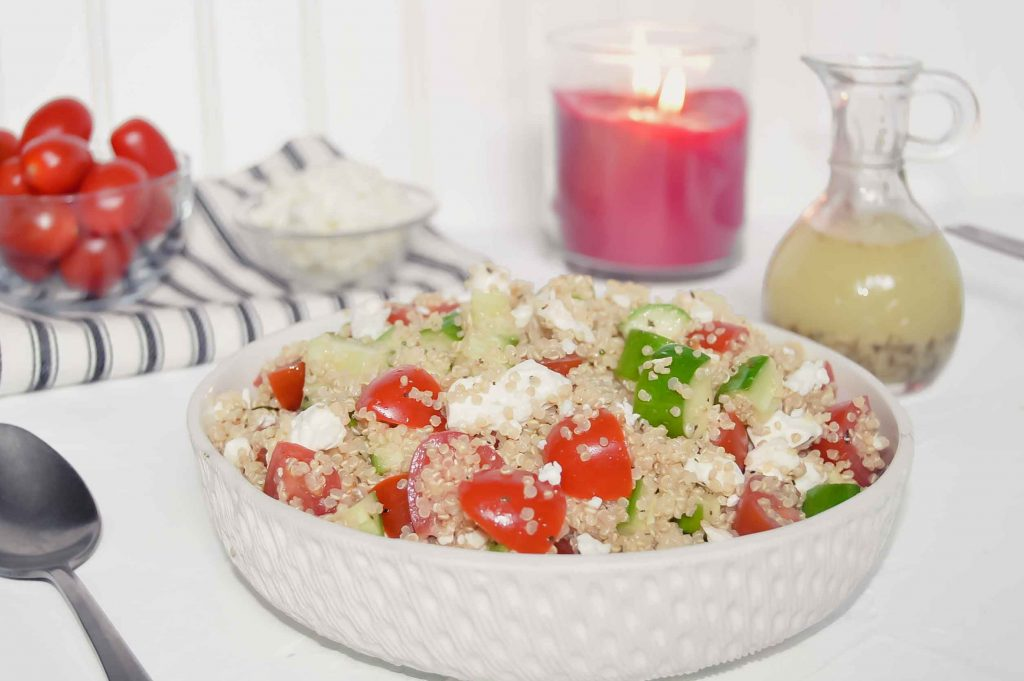Quinoa Salad with Cucumber, Tomato and Feta with a bowl of tomatoes and a bowl of feta on a black and white towel, jar of Italian Dressing and candle. www.atwistedplate.com