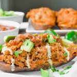 Side Image of chicken fajita stuffed sweet potato topped with ranch, avocado and salsa. In the background there is a bowl of salsa, avocado and a plate of chicken stuffed sweet potatoes. www.atwistedplate.com
