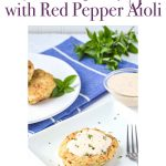 Pinterest image for tuna cake with roasted red pepper aioli on a white plate with a fork. Behind it there is a blue and white strapped towel with a round white plate of three tuna cakes. Next to it is a bowl of red pepper aioli and a sprig of basil. www.atwistedplate.com