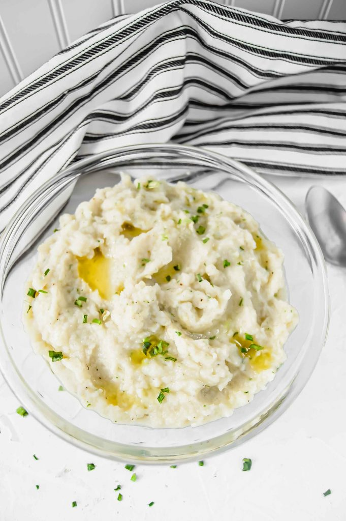 A top view of Garlic and Chive Mashed Cauliflower in a clear bowl with melted ghee and chive on top against a white background.  There is a black and white towel in the background and silver spoon to the left.  https://www.atwistedplate.com/garlic-&-chive-mashed-cauliflower/