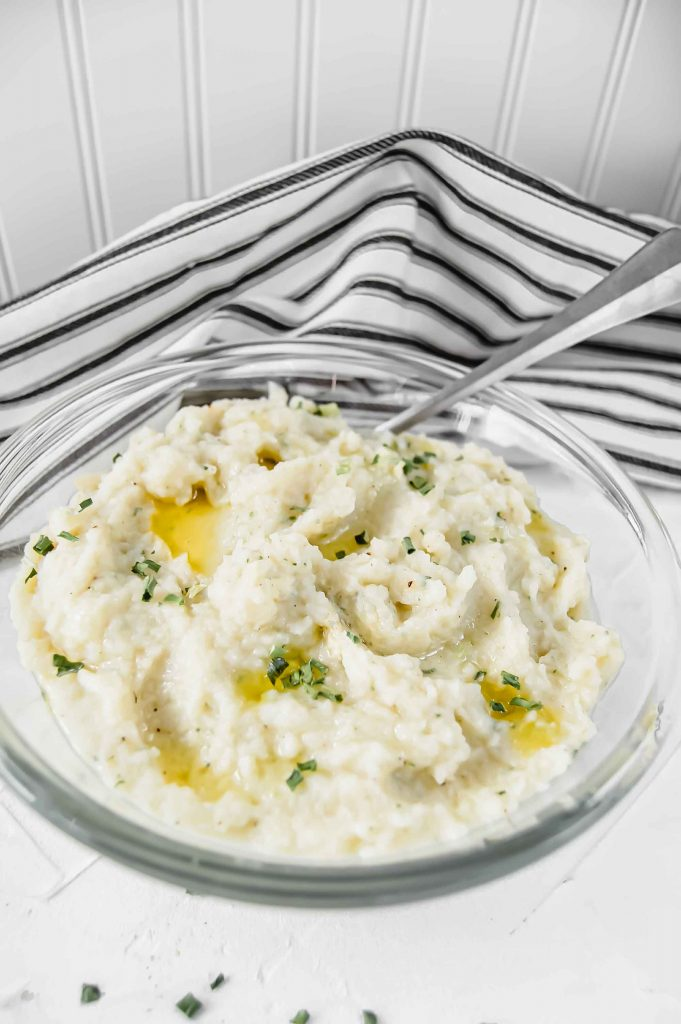 An angled view of Garlic and Chive Mashed Cauliflower in a clear bowl with melted ghee and chive on top against a white background. There is a black and white towel in the background and silver spoon to the left. https://www.atwistedplate.com/garlic-&-chive-mashed-cauliflower/