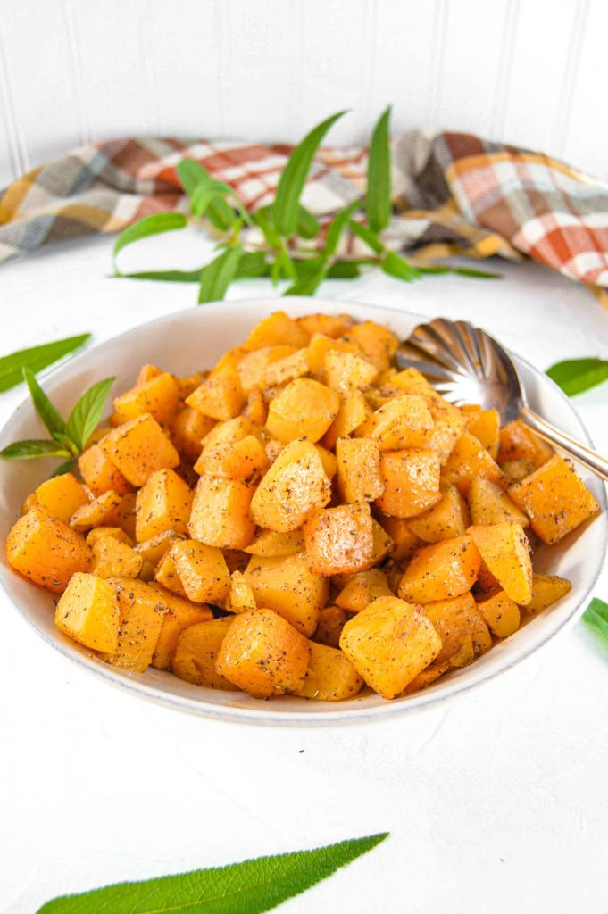 """Image of Sage and Garlic Butternut Squash in a white bowl with sage leaves scattered around and brown and yellow plaid towel behind it.  Above is a  text box with with purple script saying """"Sage and Garlic Butternut Squash"""". https://www.atwistedplate.com/garlic-and-sage-butternut-squash"""