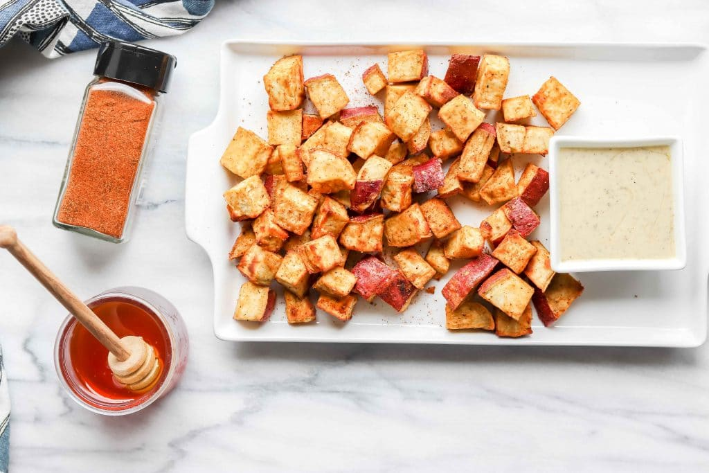 Top view Crispy Honey Bay Sweet Potatoes on a white rectangle plate with a rectangle bowl of Ranch. Plate is sitting on a Marble background https://www.atwistedplate.com/honey-bay-sweet-potatoes/