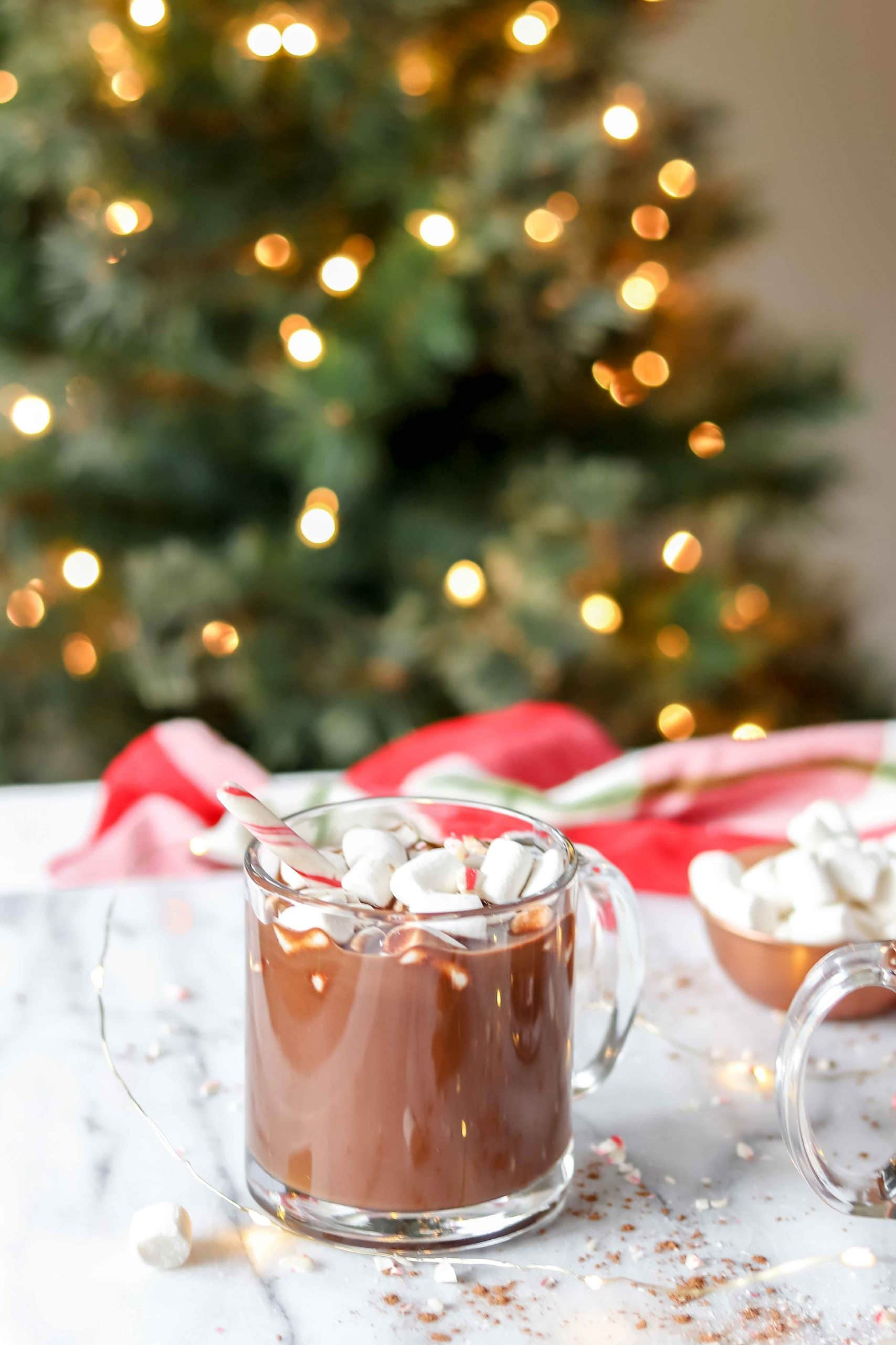 Image of a glass of Paleo Peppermint Hot Chocolate topped with marshmallows and candy cane.  There is a Christmas tree and red towel in the background.  www.atwistedplate.com/paleo-peppermint-hot-chocolate/