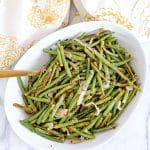 top view of Spicy Green Beans on a round white plate with a gold/white towel. www.atwistedplate.com/spicy-green-beans/