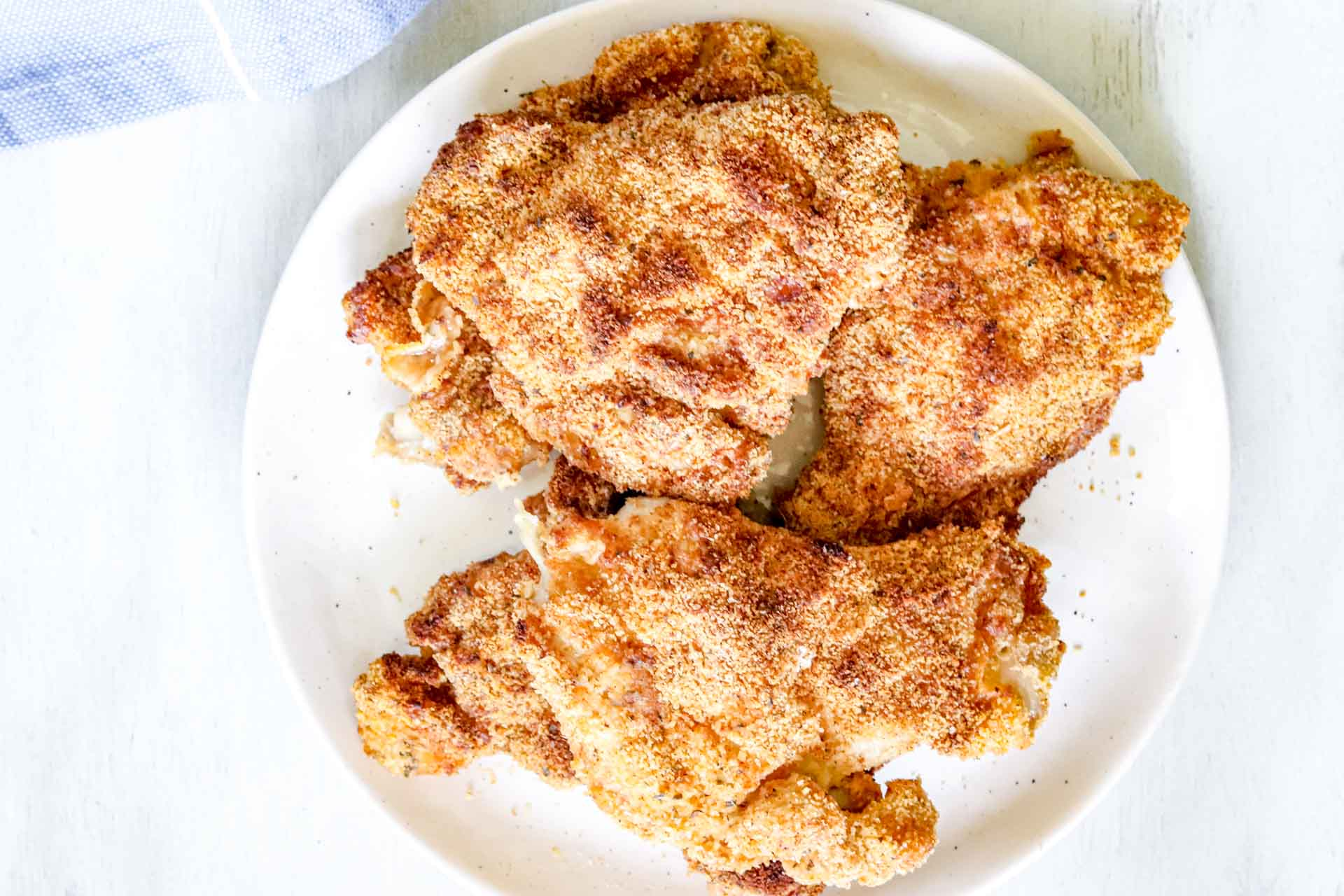Image of Whole30 Air-fryer 5 chicken thighs on a round white plate. https://www.atwistedplate.com/whole30-air-fryer-chicken-thighs/